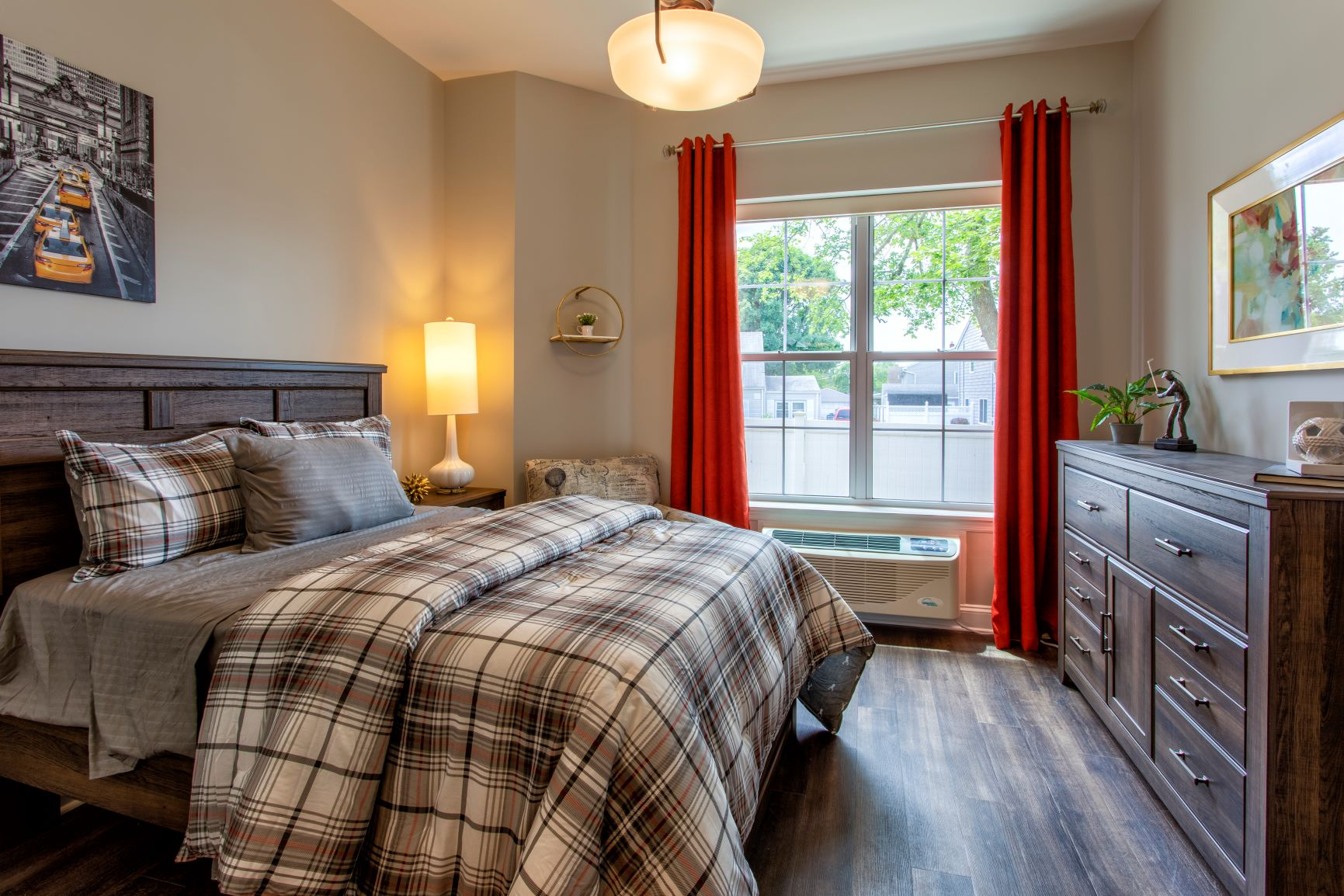 Queen bed in model apartment with window and dresser